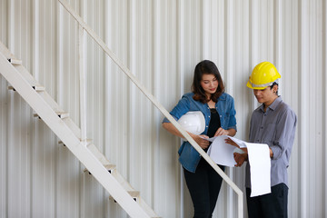 Two Asian engineers, man and woman, discussing in construction site