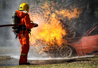 Fire fighter hosing water to  extinguish a fire over the car in accident