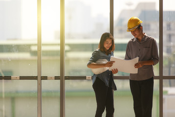 Two Asian engineer, male with yellow safety helmet and woman with white one standing and talking near high curtain wall glass frame in construction site