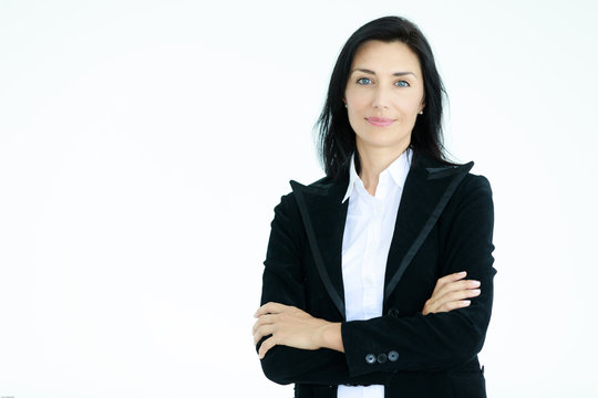Portrait of beautiful woman in black suit standing in front of white background