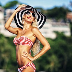 Beautiful slim tanned woman in hat and sunglasses