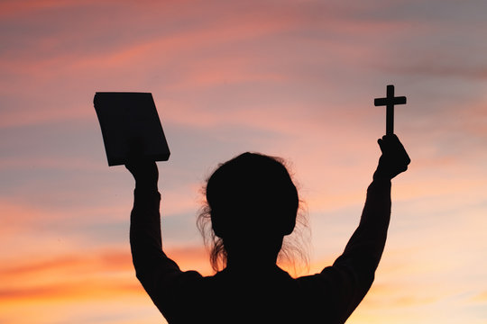 Woman with  cross and bible in hands praying for blessing from god  in the morning, spirituality and religion