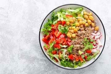 Healthy and delicious bowl with buckwheat and salad of chickpea, fresh pepper and lettuce leaves. Dietary balanced plant-based food. Vegan and vegetarian dish. Top view. Flat lay