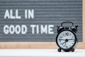black alarm clock on the background of the text all in good time