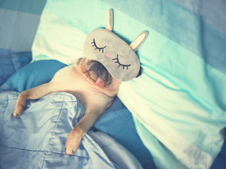 Cute pug dog sleep rest with the funny mask in the bed, wrap with blanket and tongue sticking out in the lazy time