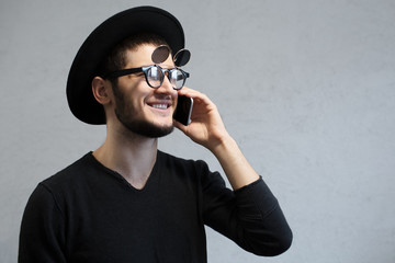 Portrait of happy hipster man calling on smartphone.
