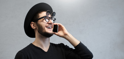 Portrait of smiling hipster man calling on smartphone.