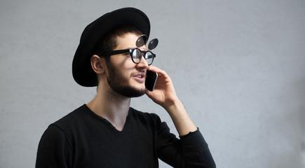 Portrait of smiling hipster man talking on smartphone.