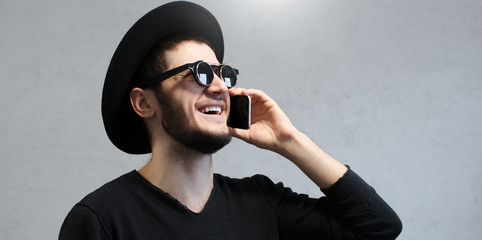 Happy hipster man with sunglasses caling on smartphone.