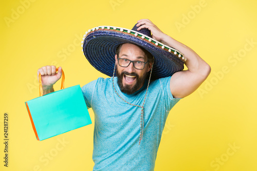 e8f8a740e00 Man wear sombrero hat shopping yellow background. Guy with beard happy in  sombrero. Souvenir gift from abroad. Man hold shopping bag.