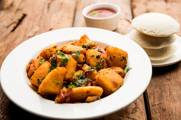 Masala fried Idlies or Idli fry - south indian Snack made using with leftover idly served with tomato ketchup. selective focus