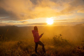 rear of happy woman stand on top mountain looking view with sunrise and mist at Doi Langka Luang, Chiang Rai province. soft focus.