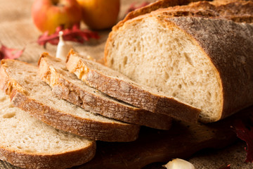Pokorojony świeży chleb w kompozycji z jesiennymi liśćmi i czosnkiem.