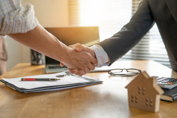 Banker business man shaking hands with client and sign contrac document for comfirm corporation or finished loan agreement for house or building property.Document in photo is fake only for stock photo