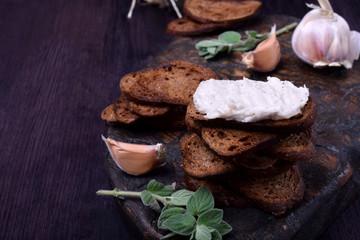 Rye bread toasts with lard paste on a black board. Ukrainian cuisine appetizer