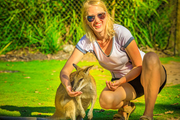 Happy blonde caucasian woman eating kangaroo in nature. Female tourist enjoys Australian animals icon of the country. Whiteman, near Perth in Western Australia. Sunny day.
