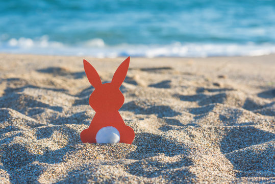 Creative easter concept photo of red paper bunny on the sand on the beach at sunset. Concept of Easter celebrations in tropical countries.