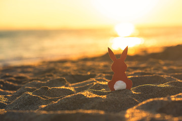 Creative easter concept photo of red paper bunny on the sand on the beach at sunset. Concept. Easter celebrations in tropical countries.
