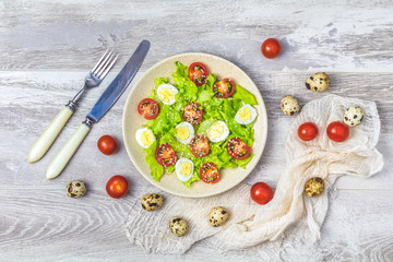 Fresh healthy salad with lettuce, quail eggs, cherry tomatoes and sesame in plate