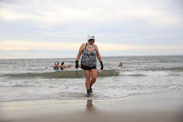A woman exits the water of the Atlantic Ocean during the Coney Island Polar Bear Club New Year's Day Plunge on Coney Island Beach