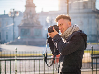 Handsome young male photographer taking photograph with professional photo camera hanging from his neck, outdoor in city street in Europe