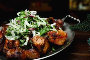 Shish kebab, kebab on a dark background. Different fried meat in plate
