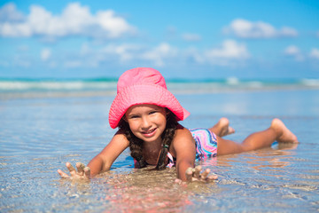 Vacation concept. Young girl with pink hat in blue water ocean.