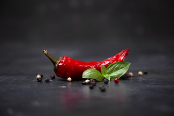In de dag Hot chili peppers chili pepper with basil and peppercorns on a rustic surface