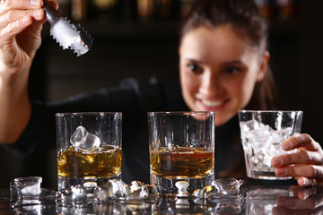 The bartender girl smiles and pours whiskey into glasses and adds ice. Photo on the bar in the restaurant. Girl out of focus.