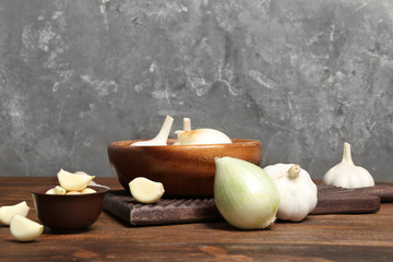Composition with onion and garlic on wooden table