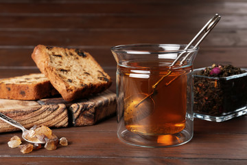 Composition with hot aromatic tea on wooden background