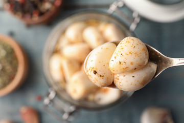 Preserved garlic in spoon over table, closeup. Space for text