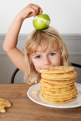 Little girl hiding behing stack of pancakes holding an apple on her head