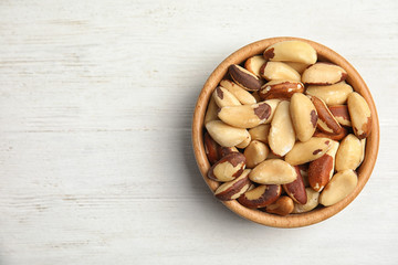 Bowl with tasty Brazil nuts and space for text on white wooden background, top view Fototapete