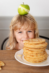Smiling little girl hiding behing stack of pancakes with an apple on top of her head
