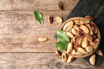 Flat lay composition with Brazil nuts and space for text on wooden background