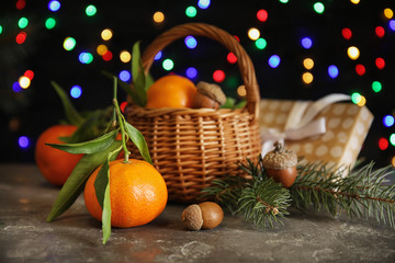 Composition with ripe tangerines and blurred Christmas lights on background