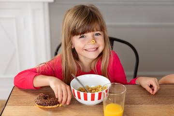 Smiling little girl with cereal loop stuck on nose at kitchen table