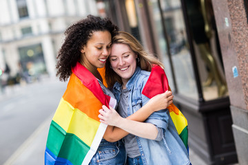 Haappy lesbian couple with a LGBT flag