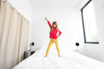 Little girl standing on bed with arm in the air