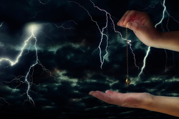 Close up of woman's hand holding a pendulum over her palm. Thunderstorm at night in background.