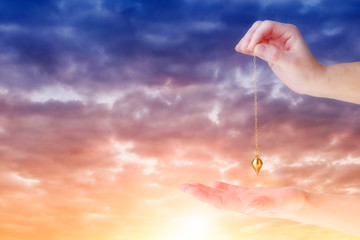 Close up of woman's hand holding a pendulum over her palm. Sunrise in background.