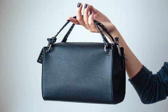 young woman with black small handbag with perfect dark violet manicure