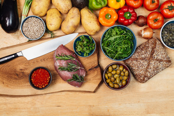 Spices, herbs, vegetables and meat on rustic wood kitchen table
