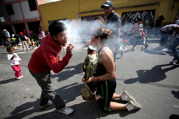 A follower blows smoke from a cigar on a statue of La Santa Muerte (The Saint of Death), often depicted as a skeletal grim reaper, as part of a cleansing ritual in Tepito neighborhood, Mexico City