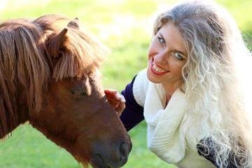funny blonde girl strokes chestnut pony muzzle, sunny day.