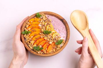 Acai bowl with blueberry smoothie, persimmon, kumquat, granola and chocolate