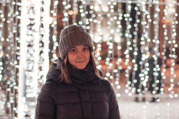 Young girl between the Christmas lights decoration outside with bokeh effect
