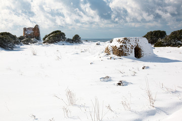Uluzzo tower after a exceptional snowfall, Salento, italy