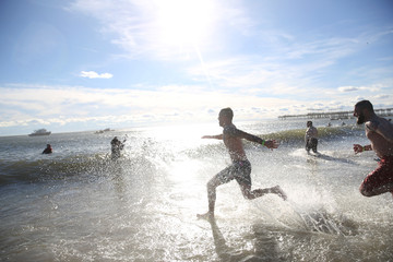Swimmers run into the water of the Atlantic Ocean during the Coney Island Polar Bear Club New Year's Day Plunge on Coney Island Beach